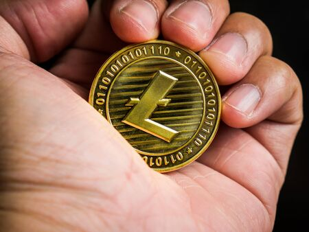 Business male hand is holding gold litecoin. Business value cryptocurrency are expensive.