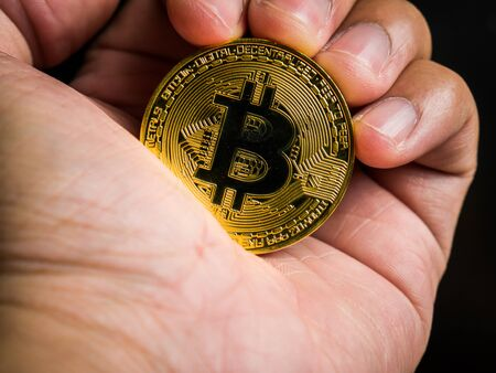 Business male hand is holding gold bitcoin. Business value cryptocurrency are expensive. Standard-Bild