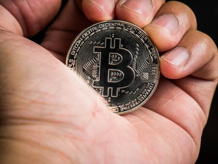 Business male hand is holding silver bitcoin. Business value cryptocurrency are expensive. Standard-Bild