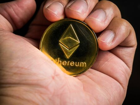 Business male hand is holding gold ethereum coin. Business value cryptocurrency are expensive.