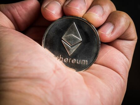 Business male hand is holding silver ethereum coin. Business value cryptocurrency are expensive. Banque d'images