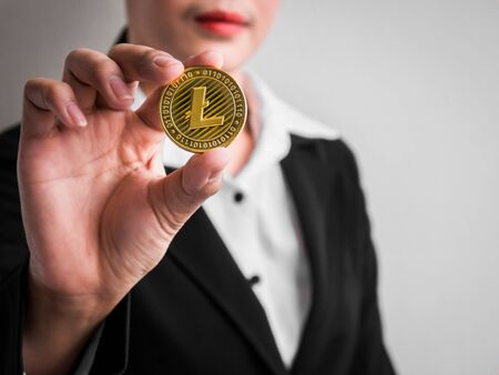 Businesswoman showing gold litecoin on the white wall is background. Investors woman holding gold litecoin from mined in the Internet. Banque d'images