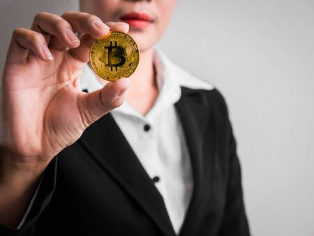 Businesswoman showing gold bitcoin on the white wall is background. Investors woman holding gold bitcoin from mined in the Internet.