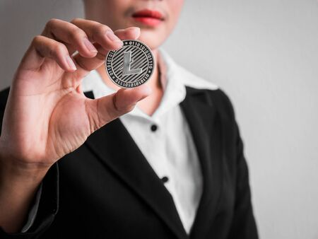 Businesswoman showing silver litecoin on the white wall is background. Investors woman holding silver litecoin from mined in the Internet. Banque d'images
