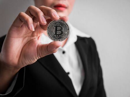 Businesswoman showing silver bitcoin on the white wall is background. Investors woman holding silver bitcoin from mined in the Internet. Banque d'images