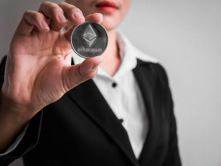 Businesswoman showing silver ethereum coin on the white wall is background. Investors woman holding silver ethereum coin from mined in the Internet.