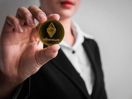 Businesswoman showing gold ethereum coin on the white wall is background. Investors woman holding gold ethereum coin from mined in the Internet. Banque d'images
