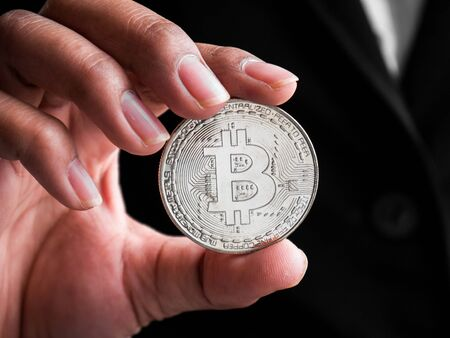 Closeup businesswoman showing silver bitcoin. Investors woman holding silver bitcoin from mined in the Internet. Banque d'images