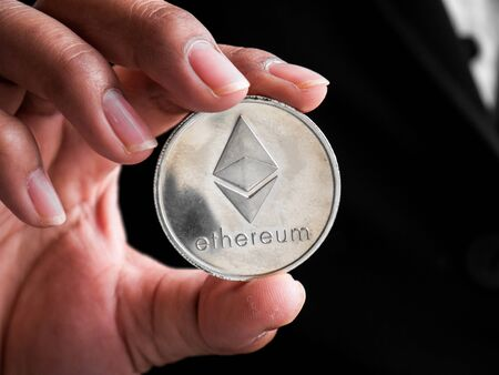 Closeup businesswoman showing silver ethereum coin. Investors woman holding silver ethereum coin from mined in the Internet. Banque d'images