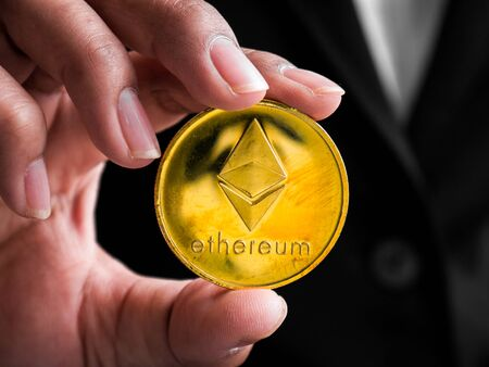 Closeup businesswoman showing gold ethereum coin. Investors woman holding gold ethereum coin from mined in the Internet. Banque d'images