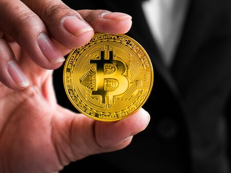 Closeup businesswoman showing gold bitcoin. Investors woman holding gold bitcoin from mined in the Internet.