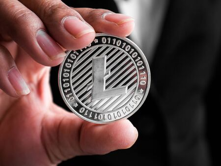 Closeup businesswoman showing silver litecoin. Investors woman holding silver litecoin from mined in the Internet.