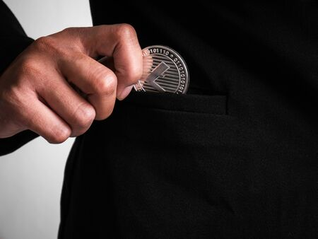 Silver litecoin was placed in the black suit of business woman had been excavated on the internet.