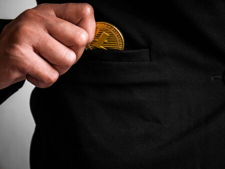 Gold litecoin was placed in the black suit of business woman had been excavated on the internet.