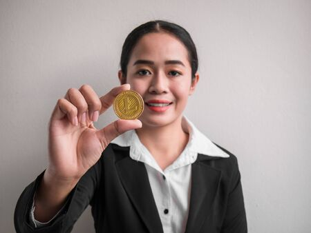 Business woman showing gold litecoin on the white wall is background. Investors woman holding gold litecoin from mined in the Internet.