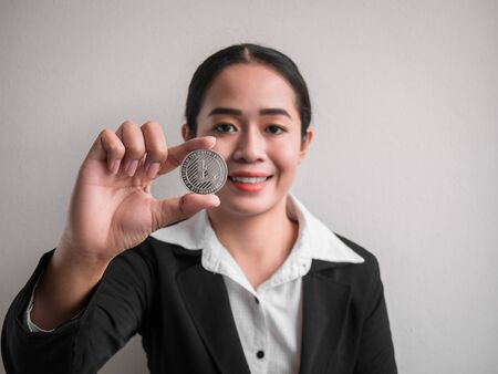 Business woman showing silver litecoin on the white wall is background. Investors woman holding silver litecoin from mined in the Internet.