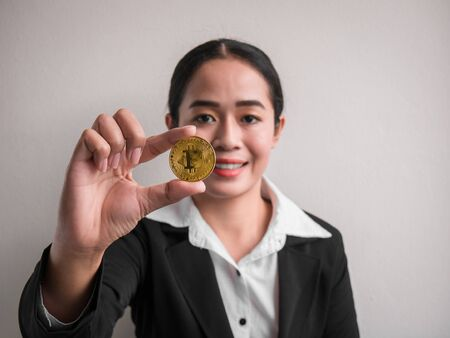 Business woman showing gold bitcoin on the white wall is background. Investors woman holding gold bitcoin from mined in the Internet.