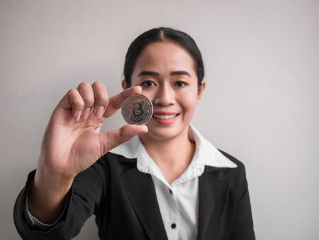 Business woman showing silver bitcoin on the white wall is background. Investors woman holding silver bitcoin from mined in the Internet.