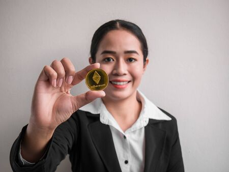 Business woman showing gold ethereum coin on the white wall is background. Investors woman holding gold ethereum coin from mined in the Internet. Standard-Bild