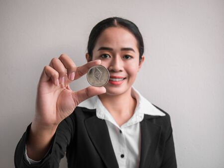 Business woman showing silver ethereum coin on the white wall is background. Investors woman holding silver ethereum coin from mined in the Internet. Banque d'images