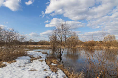 Spring flood, the river overflowed its banks. High water level in the river. Rural landscape in early spring. Clouds and trees are reflected in the water.