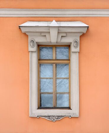 Old window on the orange wall in the Classical style