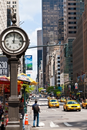 New York, United States - May 12 2013  New York urban city life with taxis passing by 5th avenue and a big street clock  Taken in the morning of May 12th 2013