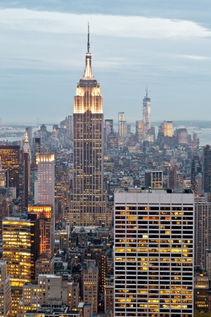 Empire State and Manhattan buildings with lights on from a high view, in the dusk of New York City, USA