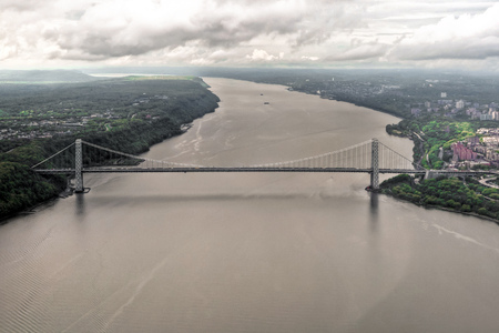 George Washington Bridge over Hudson River and Upper West Manhattan from a helicopter in a cloudy day, New York, USA