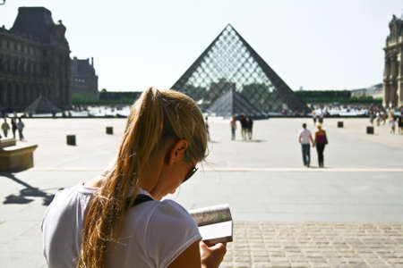 louvre pyramid: A young traveller with the Louvre Pyramid  Pyramide du Louvre  behind  This is a large glass and metal pyramid, surrounded by three smaller pyramids, in the main courtyard of the Louvre Palace