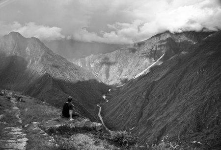 contemplates: A traveller contemplates the amazing scene in the mountains near Machu Picchu, Cusco, Peru