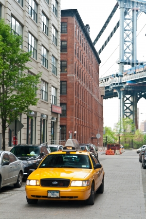 New York, United States - May 9, 2013  Urban scene of Brooklyn with Manhattan Bridge in the background with typical yellow taxis going along the streets  Taken on a beautiful morning of summer at NYC on May 9th, 2013
