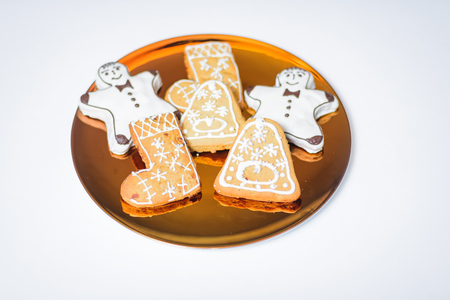 Christmas cookies on the gold plate on the white background