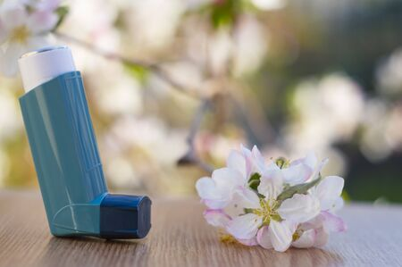 Inhaler for asthma with a blossoming apple tree.