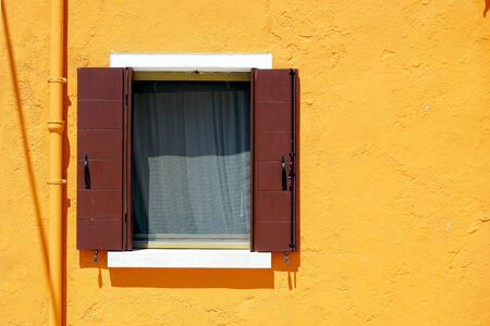 Brown Window in Burano on orange color wall building architecture, Venice, Italy Stok Fotoğraf