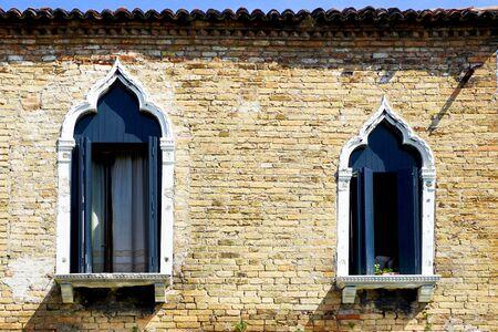 Murano: two windows and ancient brick wall building architecture in Murano, Venice, Italy