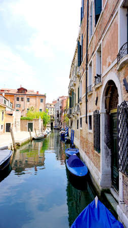 vetical: canal and boats with ancient buildings vetical in Venice, Italy