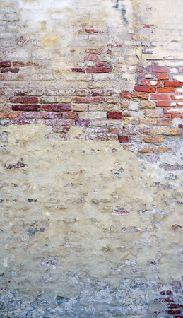 decay wall mixed with brick background vetical in Venice, Italy Stock Photo