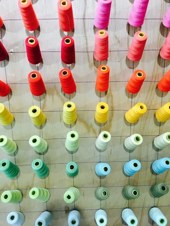 Colorful thread sewing material on wood background Stok Fotoğraf