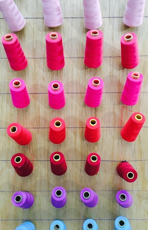 Closeup colorful thread sewing material on wood background Stock Photo