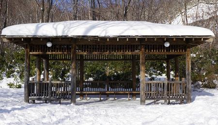 Snow and wooden pavilion elevation in the forest Noboribetsu onsen snow winter national park in Jigokudani, Hokkaido, Japan