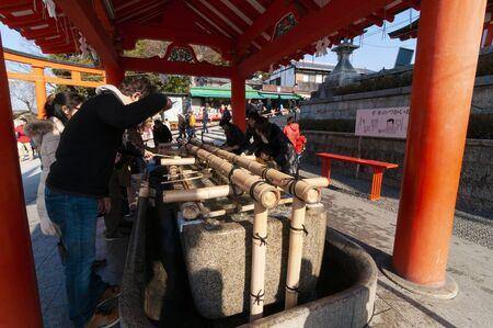 People purify themselves at Temizu (purification) basin in Fushimi Inari Shrine.