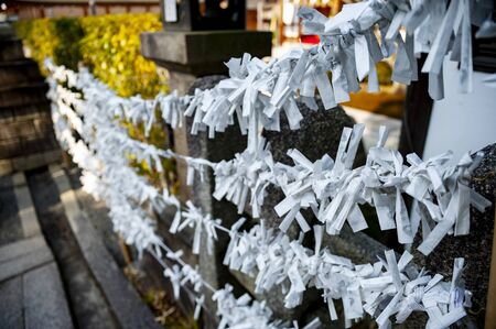Omikuji (paper strips with random fortunes) at Fushimi Inari Shrine. Редакционное