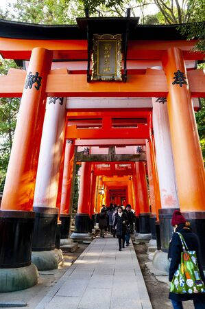 A walking path leads through a tunnel of torii gates (japanese wooden gates) at Fushimi Inari Shrine (sacred place) in Kyoto, Japan.
