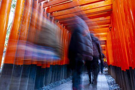 People walking through the pathway of Torii Gates (Japanese wooden gate) at Fushimi Inari Shrine (Japanese Temple) in Kyoto. Редакционное