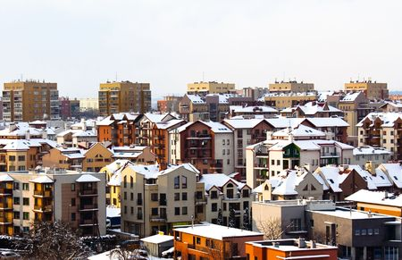 executive apartment: Snow in the city on the houses roofs.
