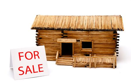 Home for sale sign and wooden model house isolated on white. Foresters lodge or chalet  maybe. photo