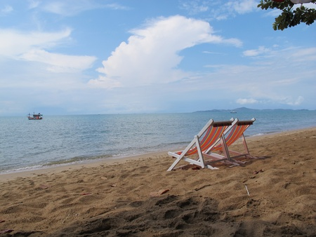 Double beach beds and small boat under blue sky