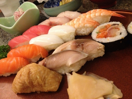 Many types of sushi in red dish