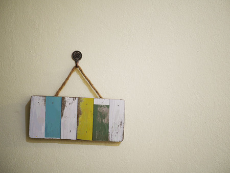 Isolated empty wood sign hanging at the white wall background